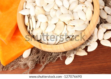 Pumpkin seeds in wooden bowl, on wooden background