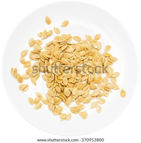 pumpkin seeds on a plate on a white background