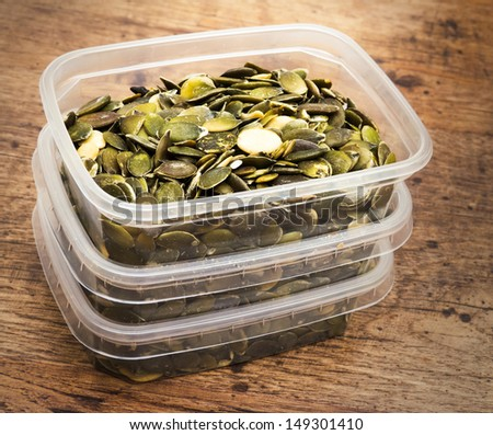 Pumpkin seeds stacked in plastic boxes on wooden table - stock photo