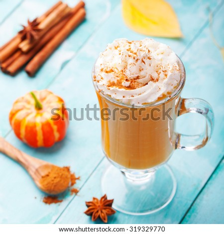 Pumpkin smoothie, spice latte with whipped cream on top on a turquoise wooden background - stock photo