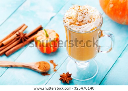 Pumpkin smoothie, spice latte with whipped cream on top on a turquoise wooden background. copy space  - stock photo