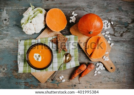 Pumpkin soup at the table with carrots, slices of pumpkin, bred,cauliflower and pumpkin seeds - stock photo