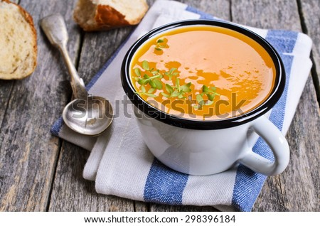 Pumpkin soup in a metal pot on a wooden surface - stock photo