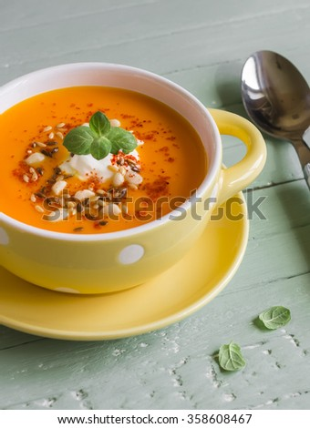 pumpkin soup in a yellow bowl on a wooden surface