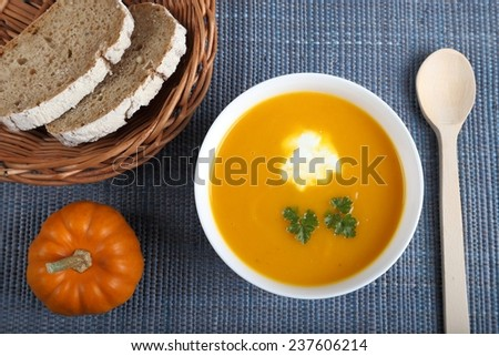 Pumpkin soup in white bowl on a blue background.  - stock photo