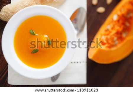 Pumpkin soup in white bowl on wood table - stock photo