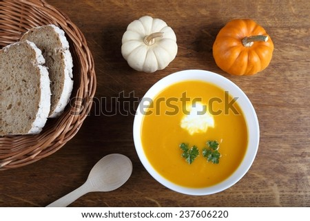 Pumpkin soup in white bowl on wooden background.  - stock photo