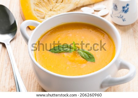 Pumpkin soup in white bowl topped with fresh mint  - stock photo