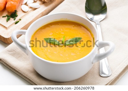 Pumpkin soup in white bowl topped with fresh mint