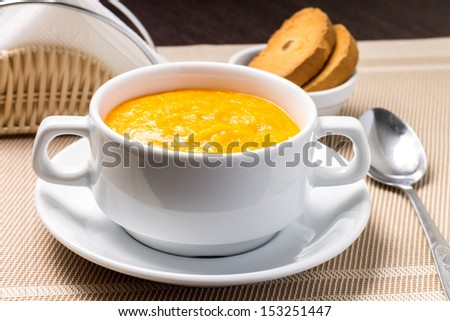 Pumpkin soup in white bowl with crouton