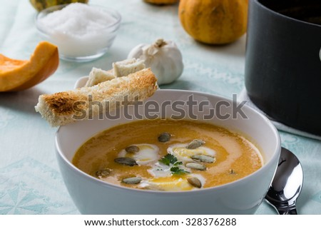 pumpkin soup in white bowl with toast