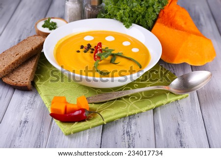 Pumpkin soup in white plate and pumpkin slice on napkin, on wooden background - stock photo