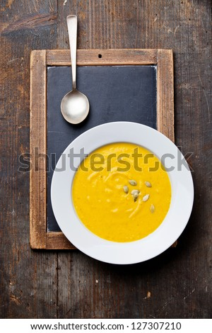 Pumpkin soup in white plate on vintage slate chalk board - stock photo