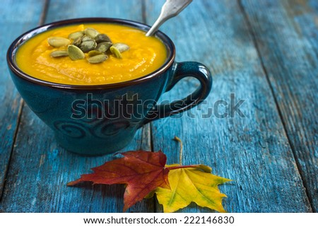 pumpkin soup on a bowl on a blue wooden background - stock photo