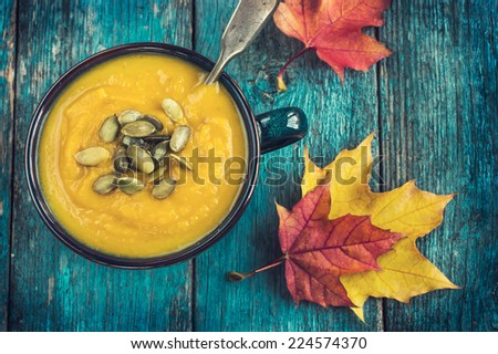 pumpkin soup on a bowl on a blue wooden background, top view, toned - stock photo