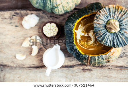 Pumpkin soup on rustic wooden background. Macro shot with shallow depth of field. - stock photo