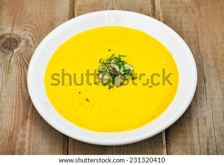 Pumpkin soup on rustic wooden table, close up view