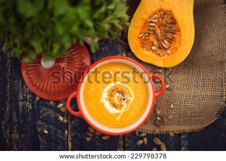 Pumpkin soup on wooden background - stock photo