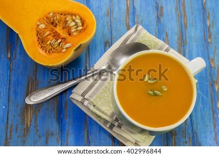 Pumpkin soup puree, half raw pumpkin, napkin, spoon, blue wooden table. - stock photo