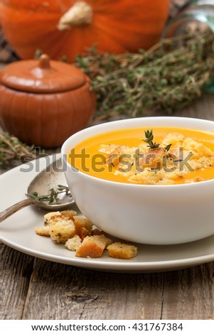pumpkin soup - puree with croutons  in a white bowl on the old wooden background - stock photo