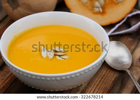 Pumpkin soup served in white bowl on wooden background, selective focus