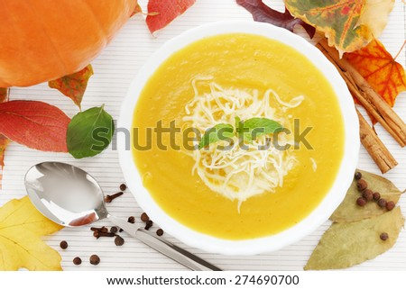Pumpkin soup with autumn leaves, spices and a pumpkin - stock photo