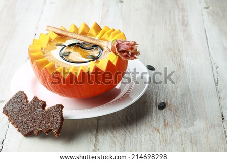 Pumpkin Soup with Bat Toast Crouton and Broomstick Bread Stick Served in Half a Pumpkin with Copyspace - stock photo