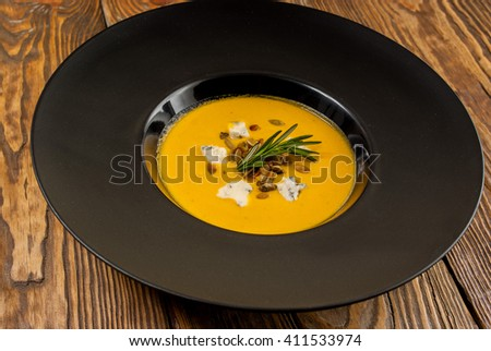Pumpkin Soup with blue cheese and pumpkin seeds with rosemary on a wooden table - stock photo