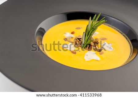 Pumpkin Soup with blue cheese and pumpkin seeds with rosemary selective focus - stock photo