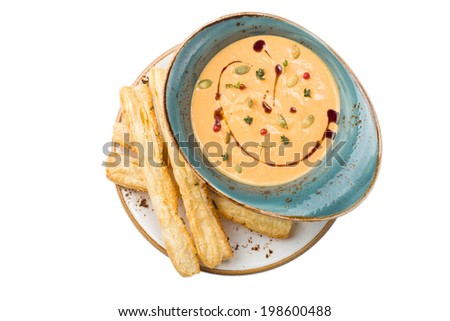 Pumpkin soup with bread sticks isolated on white background - stock photo