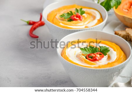 Pumpkin soup with cream and parsley on a grey concrete or stone background, selective focus, copy space