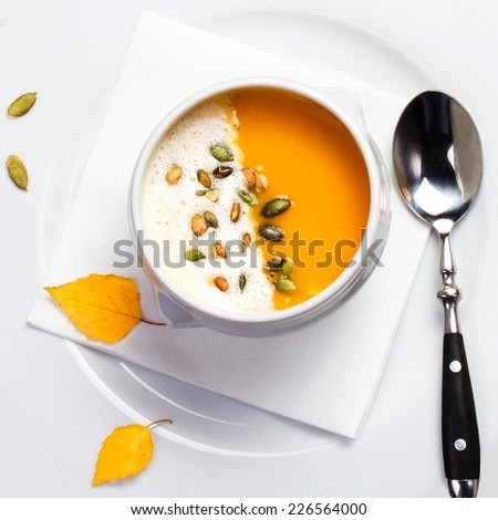 Pumpkin soup with cream and pumpkin seeds on a white plate macro. Yellow Pumpkin soup made for Thanksgiving. Studio shot for restaurants  - stock photo