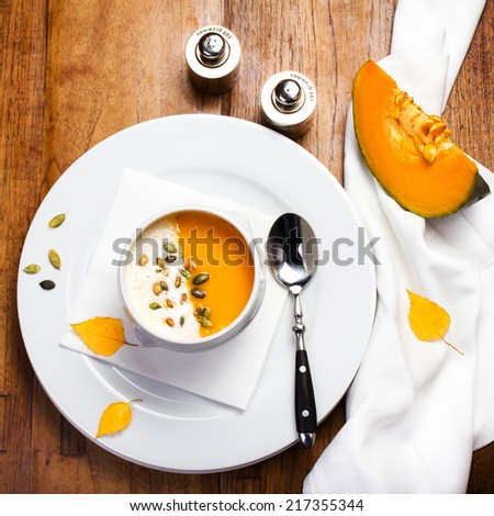 Pumpkin soup with cream and pumpkin seeds on a white plate on wooden background - stock photo