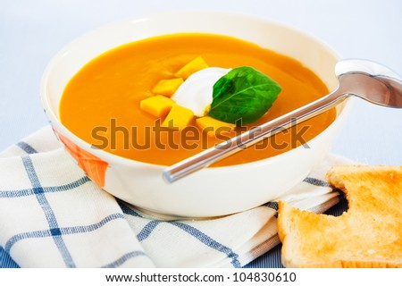 Pumpkin soup with cream in a bowl with painted flower and toast as a garnish. - stock photo