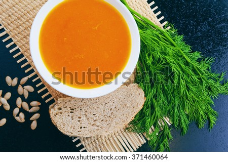 Pumpkin soup with dill and bread on a mat and pumpkin seeds - stock photo