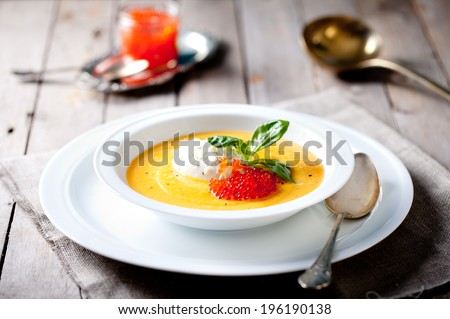 Pumpkin soup with lemon cream and red salmon caviar in a white plate on a wooden background. Selective focus