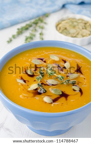 Pumpkin soup with pumpkin oil and seeds close-up