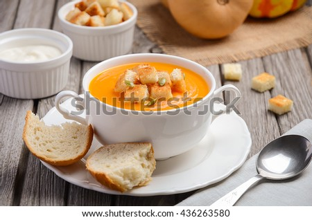 Pumpkin soup with pumpkin seeds and croutons on wooden table, selective focus