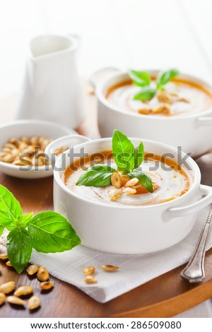 Pumpkin soup with pumpkin Seeds, cream and basil on white wooden background, selective focus - stock photo