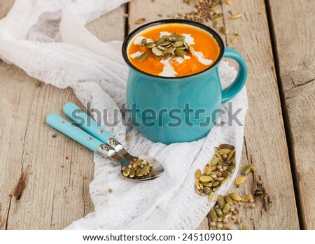 Pumpkin soup with pumpkin seeds in a cup - stock photo