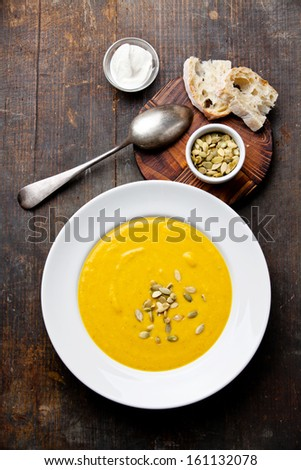Pumpkin soup with pumpkin Seeds on wooden background - stock photo