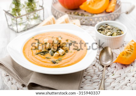 Pumpkin soup with seeds and croutons and herbs