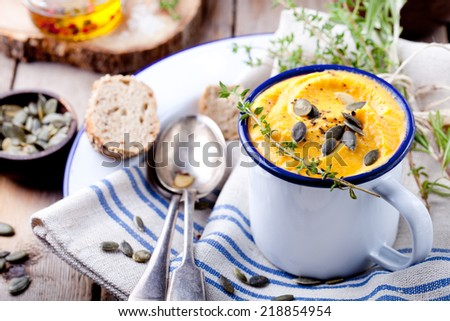 Pumpkin soup with seeds and thyme in an enamel mug on a wooden background - stock photo