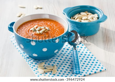Pumpkin soup with seeds in blue bowl on wooden background/Pumpkin soup   - stock photo