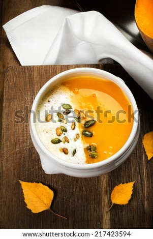 Pumpkin Soup with whipped cream and pumpkin seeds in a white plate over wooden background.  Beautiful autumn Pumpkin thanksgiving soup - stock photo