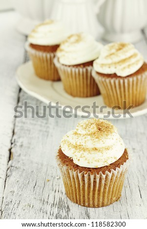 Pumpkin spice cupcakes frosted with cream cheese icing and sprinkled with brown sugar. Shallow depth of field. - stock photo