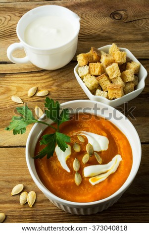 Pumpkin squash cream soup with cream and pumpkin seeds in the white bowl, cream in creamer and croutons in serving dish on wooden background, vertical. Pumpkin soup. Soup. Creamy soup. Vegetable soup  - stock photo