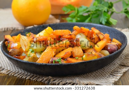 Pumpkin stew with vegetables in frying pan, close up view