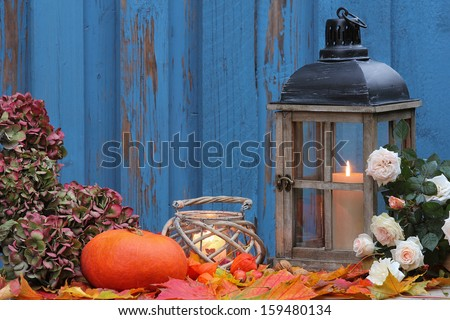 Pumpkin, storm lamp and lantern with white roses - stock photo