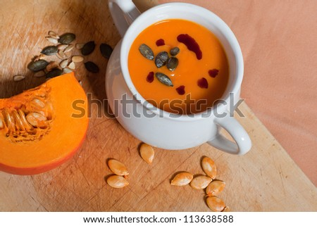 Pumpkin vegetable cream soup in white bowl with pumpkin on cutting board - stock photo
